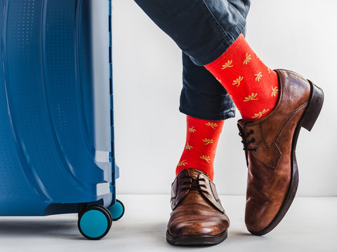 Stylish suitcase, men's legs, multicolored socks and new shoes on a white, isolated background. Close-up, indoors. Studio foto. Concept of style, fashion, beauty and vacation