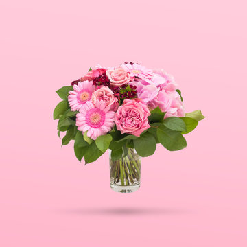Beautiful bouquet flowers in glass vase floating on pink background, minimal design