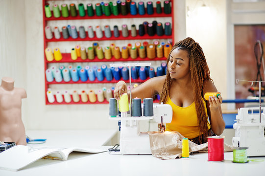 Young african dressmaker woman sews clothes on sewing machine and selects threads at tailor office. Black seamstress women.