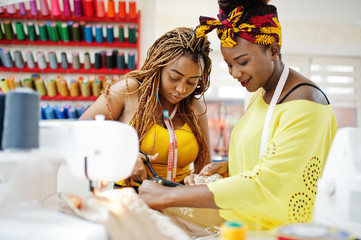 Two african dressmaker woman sews clothes on sewing machine and work with scissors at tailor...