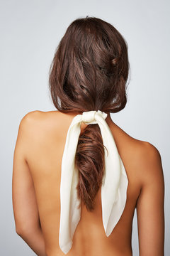 Close-up back shot of a brunette lady with a white silk hair scarf fixed on the scrunchie. The shirtless woman with a ponytail is posing on the gray background.