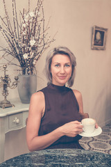 Toned picture of front view of beautiful blonde lady sitting in cafe or restaurant near window and drinking coffee