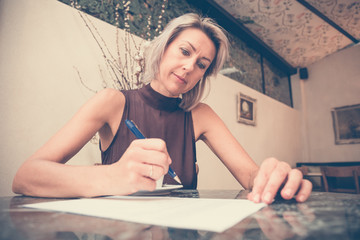 Toned picture of beautiful blonde lady sitting in cafe or restaurant near window and signs documents