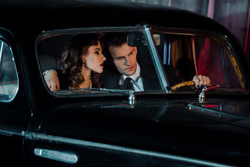 selective focus of man touching steering wheel and sitting near attractive woman in retro car