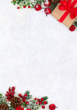 Christmas decoration, banner. Gift box with red ribbon, bow, twigs christmas tree, red berries and apples on snow with space for text. Top view, flat lay