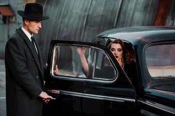 handsome man touching car door near beautiful woman
