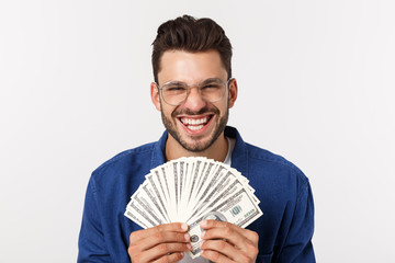 Attractive man is holding cash money in one hand, on isolated white background