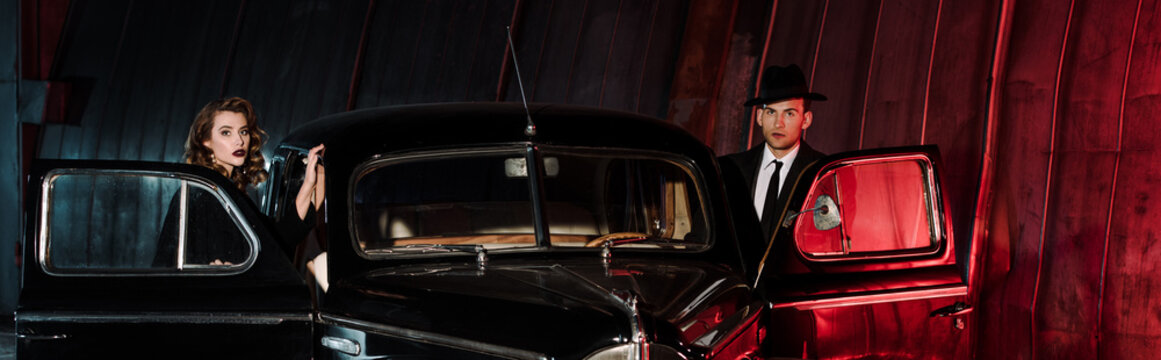 panoramic shot of attractive woman and handsome gangster standing near retro car