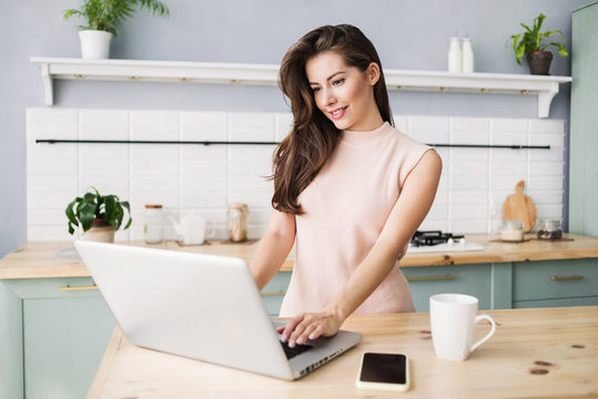 Cute smiling woman using laptop computer in the kitchen. Online shopping concept