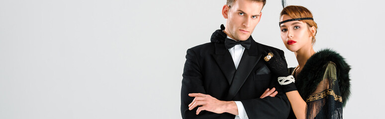 panoramic shot of handsome man in suit standing with aristocratic woman isolated on white