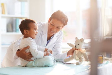 Young female doctor in white coat showing toy to her little patient and playing with him at hospital