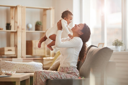 Side view portrait of happy African-American mother holding cute baby boy while playing at home, copy space