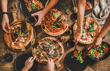 Family or friends having pizza party dinner. Flat-lay of people cutting and eating Italian pizza and drinking red wine from glasses over wooden table, top view. Fast food lunch, gathering, celebration