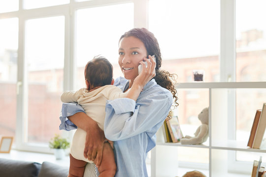 Waist up portrait of young African-American mother speaking by phone while holding baby in sunlit apartment, copy space