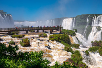 View to spectacular Iguazu Falls with visitor platform and blue sky