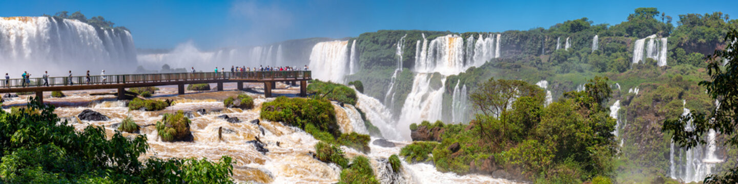 Panorama of spectacular Iguazu Falls with visitor platform and blue sky