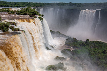 View of powerful Iguazu Falls near Devil´s Throat with brown and white water in lush green vegetation