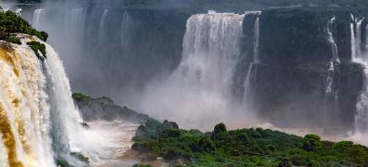 Panoramic view to Iguazu Falls in sunshine and mist