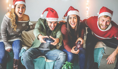 Group of happy friends having fun with video games console on christmas time - Young millennial...