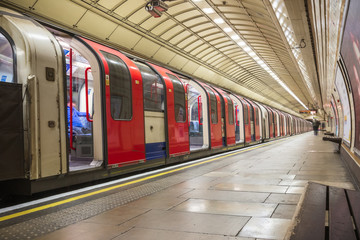 Train waiting to depart at platform of London Underground tube (Gants Hill) station