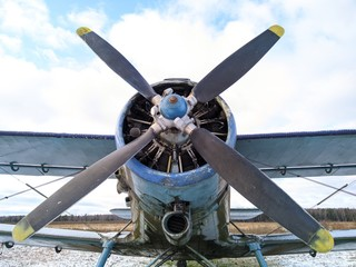 A four bladed black propeller on the nose of a green biplane aircraft against a blue sky
