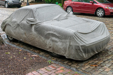car covered by tarpaulin in the street