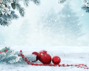 Holiday background with red Christmas balls and fir tree branch.