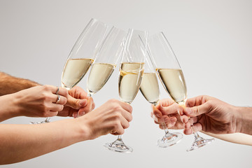 cropped view of men and women clinking champagne glasses with sparkling wine isolated on grey