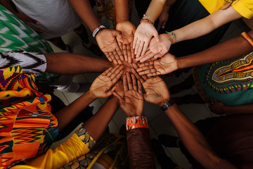 Palms up hands of happy group of multinational African, latin american and european people which stay together in circle
