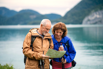 A senior pensioner couple hikers standing by lake in nature, using map.