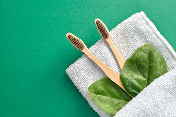 Bamboo toothbrush on towel with green leaves