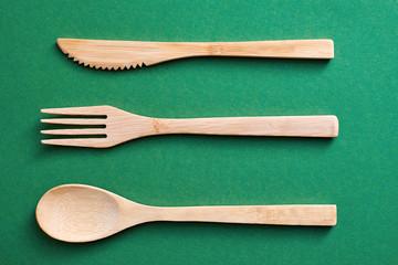 Wooden utensils on green paper background