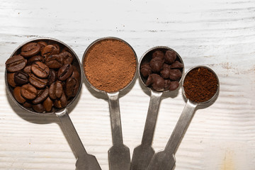 Coffee grains, cocoa, chocolate drops and ground coffee on a white wooden background