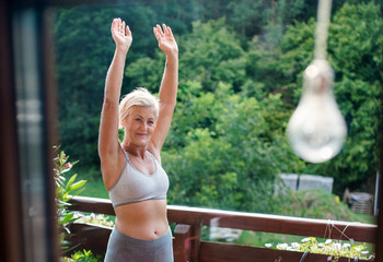 A senior woman with sports bra outdoors on a terrace in summer, exercising.