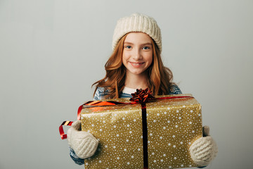 A teenager in a knitted hat, sweater and gloves is smiling. A girl hugs her Christmas present from her parents. She was pleasantly surprised by the seasonal discounts.