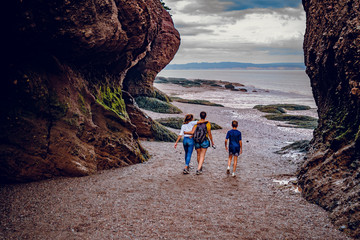 Self adhesive Wall Murals Cappuccino Familly people walking at Sunset in Hopewell Rocks at low tide