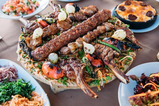 Traditional Turkish Adana kebab or kebap meat food, appetizers, raki and salgam on table from top view in turkish restaurant.