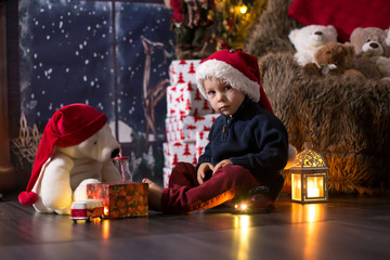 Sweet toddler boy, playing with wooden train at home at night on Christmas