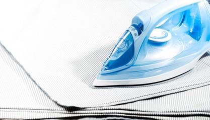 Fototapeta Close-up blue modern iron on ironed light bedding. obraz