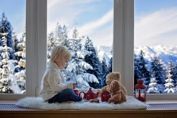 Sweet blonde child, boy, sitting on window shield, drinking tea with teddy bear friend toy