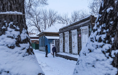 Young women stand next to a house with traditional wooden carved architraves in Blagoveshchensk