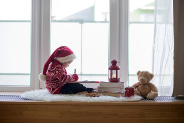 Sweet blonde child, boy, sitting on window shield with teddy bear friend toy, writing letter to Santa Claus and reading book