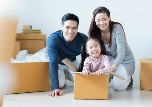 Asian Family having fun together. Young Mother and Father playing with their Daughter while her sitting in cardboard box at the new house.