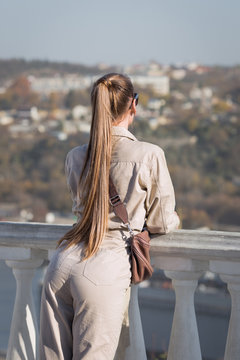 Young woman with ponytail stands leaning on balustrade and looks into distance, rear view