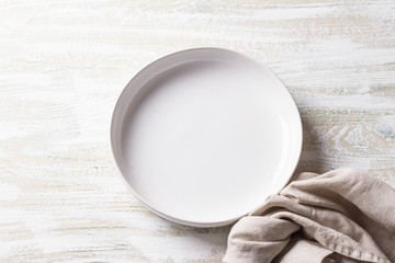 White plate with linen napkin on white wooden background