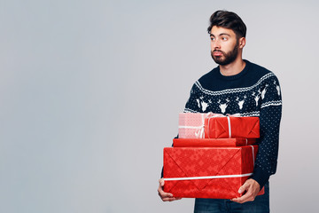 Unhappy tired man holding Christmas presents looking away. Isolated
