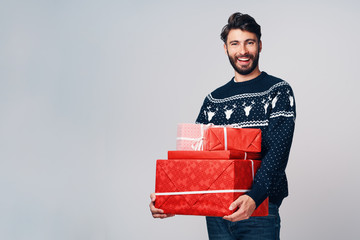 Happy young man holding Christmas presents. Isolated