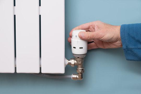 Hand turning down temperature on TRV radiator thermostat valve