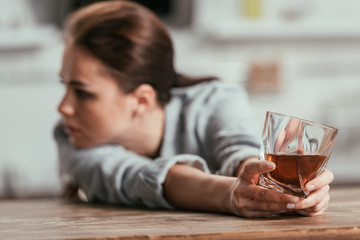 Selective focus of sad woman holding whiskey glass at table