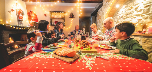 Large multi generation family having fun at christmas dinner party - Winter holiday xmas concept with grandparents, parents and children eating together at home - Focus on grandpa face